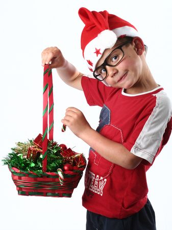 Young boy with santa hat and glasses stealing candy from Christmas basket photo