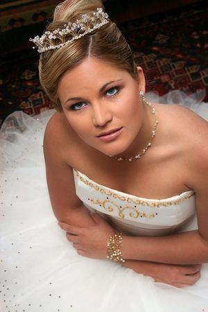prominent: Bride sitting on floor looking up at camera. Prominent eyes Stock Photo