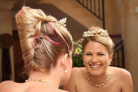 hair do: Young bride looking in mirror showing hair do Stock Photo