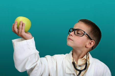 Boy dressed up as a doctor with a stethoscope looking at an apple Stock Photo - 603422
