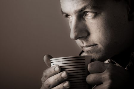 sepia toned: Man drinking warm beverage. Low key image. Sepia toned. Stock Photo