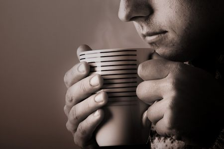 steam mouth: Man drinking warm beverage. Low key image. Sepia toned. Steam from cup