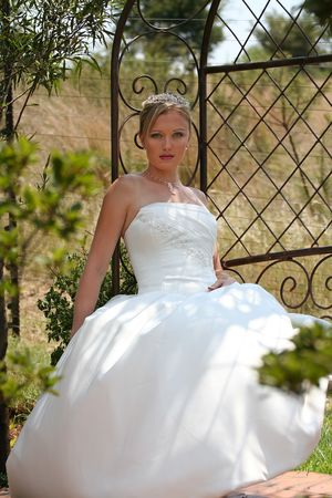 Young blond bride waiting on bench in garden Stock Photo - 914945