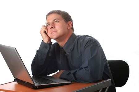 envisage: Male dressed in black sitting at office desk with laptop. Isolated; Dreaming