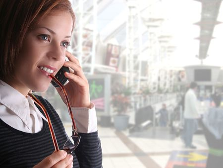 Attractive lady speaking on cellphone in shopping centre. Centre faded to background to allow for copyspace Stock Photo - 1462828