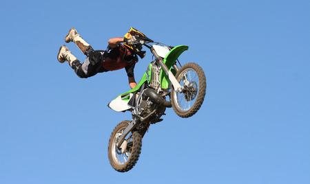 mx: Extreme spoirts. MX Bikes against blue sky doing jump.