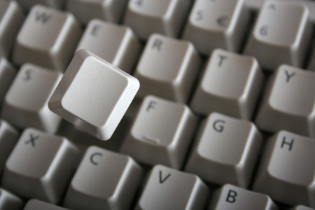 Key jumping out of keyboard with a spring. Blank key face photo