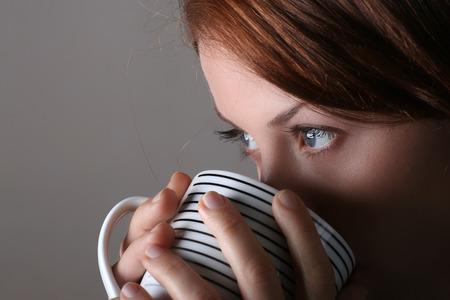 gril: Attractive lady drinking hot beverage. Short DOF. Sharp striking eyes Stock Photo