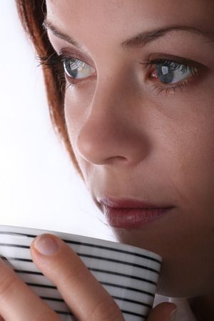 Attractive young woman holding a mug / cup. Stock Photo - 1416165