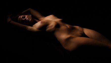 Low-key nude woman body