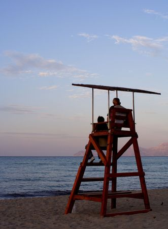 Two people sitting on a lookout tower on the beach at sunset... photo
