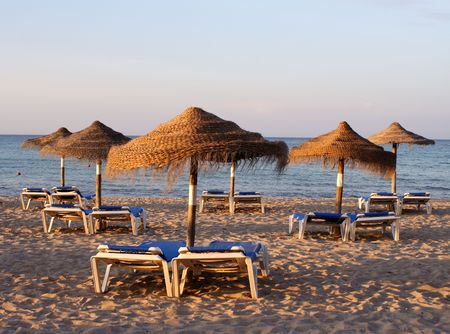 sunshades: A couple of deck-chairs and sunshades late in the afternoon at a lonely beach... Stock Photo