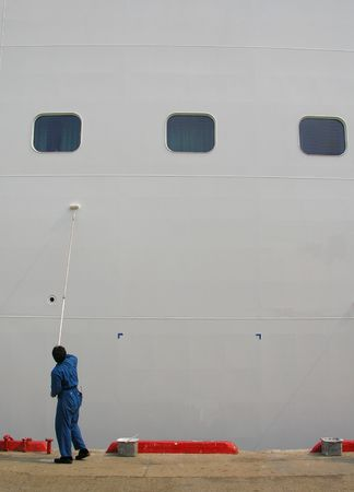 man painting: A lonely man painting a large ship