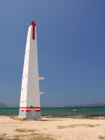 middleages: Red-white obelisk on the beach