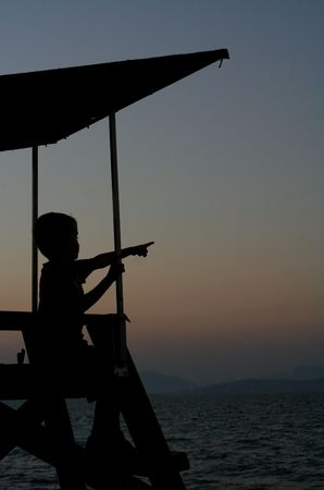 A child on a lookout tower at sunset on the beach... photo