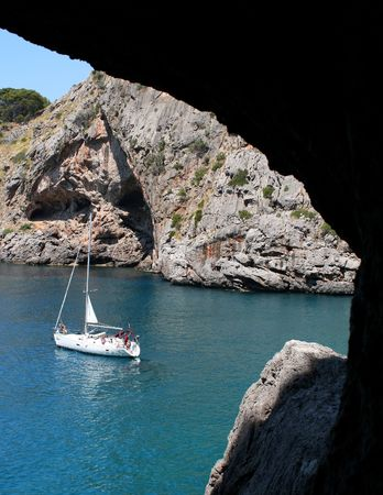 anchoring: A view on an anchoring sailboat through a window in a cave...