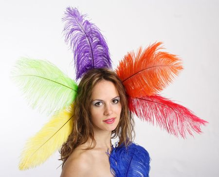 Beautiful brunette woman holding colored feathers photo