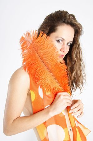 Beautiful brunette woman dressed with a silk foulard holding a large orange feather photo