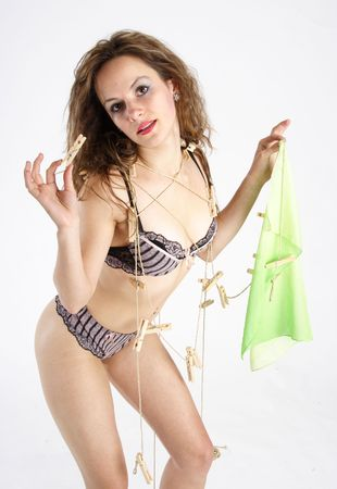 Beautiful brunette woman hanging up clothes on a clothesline photo