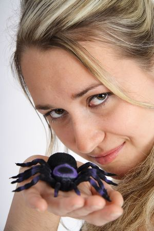 Portrait of a beautiful blond woman playing with a black spider photo