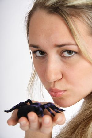 Portrait of a beautiful blond woman kissing a black spider photo