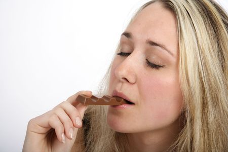 Portrait of a beautiful blond woman eating a bar of chocolate photo