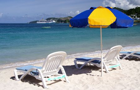 Two deck chairs with a parasol on a lonely beach...