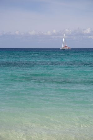 Beautiful caribbean beach with a sailing boat in the background photo