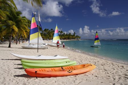 Beautiful caribbean beach with a colorful jolly boats and kayaks photo