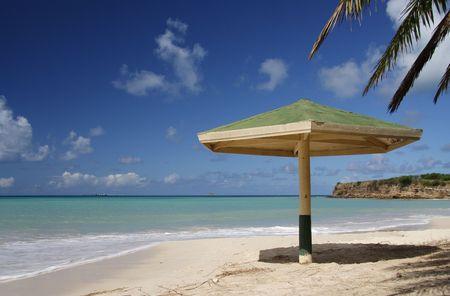 Parasol with palm leaf at a caribbean beach photo