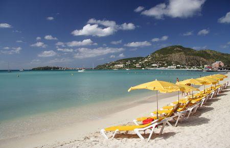 Canvas chairs and sun shades at a beautiful caribbean beach photo