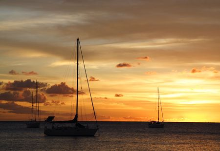 Colourful caribbean sunset with sailboats photo