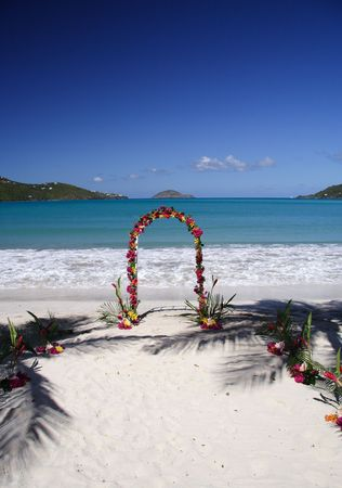 Archway decorated with colorful flowers on a caribbean beach Stock Photo