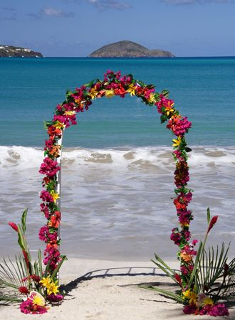 archway: Archway decorated with colorful flowers on a caribbean beach Stock Photo