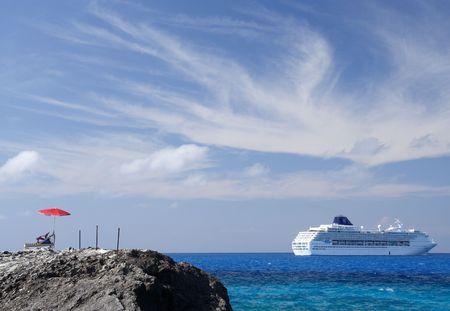 cruiseship: Sombrilla y silla de lona con un crucero en el fondo
