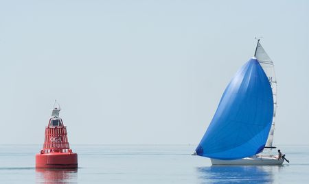 A cruising sailboat in the morning dust with red buoy Stock Photo - 922424