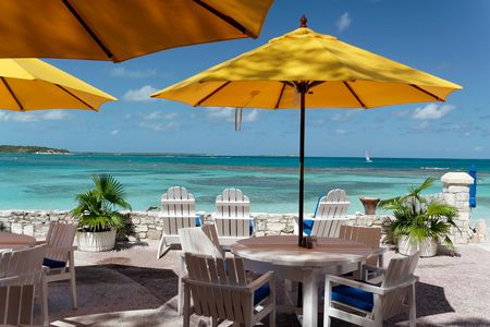 yello: Terrace of a restaurant with yello sun shades on a beautiful caribbean beach