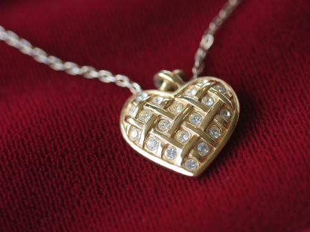 Close up of a heart necklace in gold and fake diamonds on red velvet.
