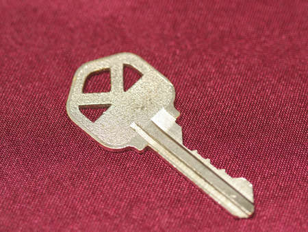 Close up of a gold key on red