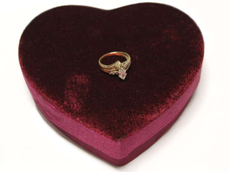 Isolated red velvet heart with an engagement ring on top Stock Photo