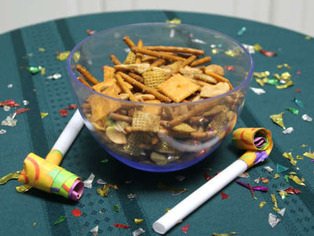 Close up of party blowers on a teal tablecloth, with snack mix and confetti