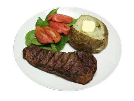 Isolated steak dinner with a baked potato and salad Stock Photo