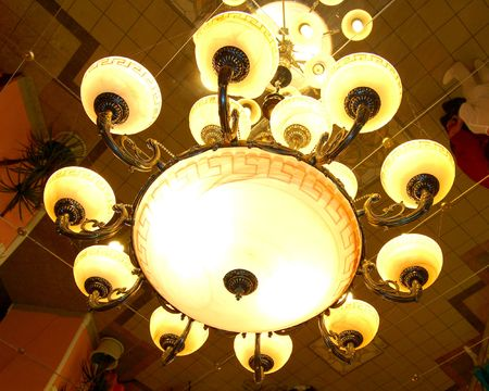 Close-up of Modern Classics Chandelier. Mirror Ceiling. photo