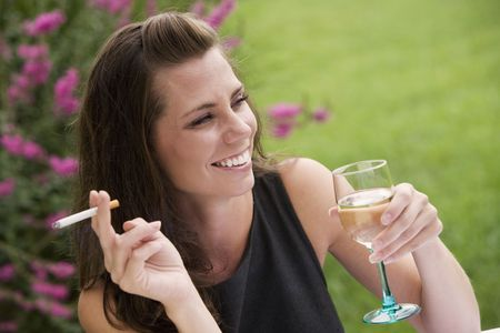Model Release 351  Young woman relaxing with a glass of wine and a cigarette in an outdoor cafe photo