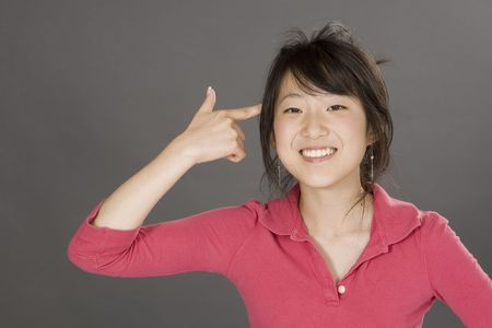 Portrait of a beautiful Asian teenager posing on a gray background with finger pointing at head photo
