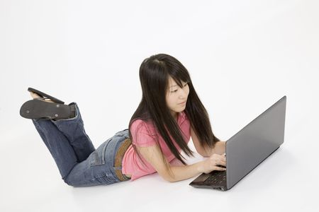 conputer: Portrait of Asian teenager working with a laptop conputer on a white background
