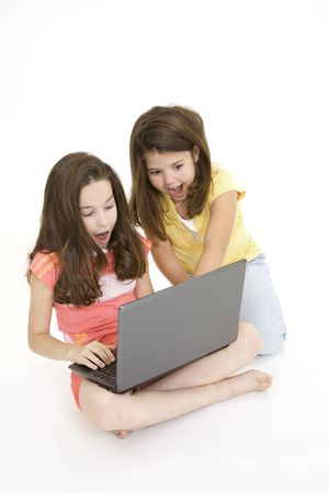 Sisters playing on a laptop computer on a white background