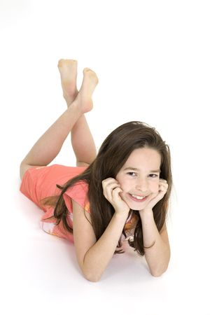 Eight year old female child laying on white background smiling wearing casual clothes Stock Photo