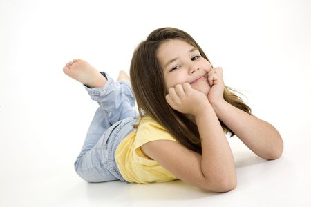 Five year old female child laying on white background smiling wearing casual clothes Stock Photo
