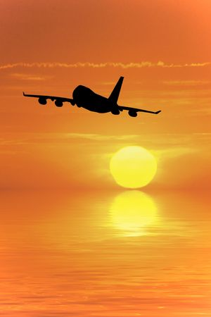 Airliner flying into the sunset over the ocean Stock Photo